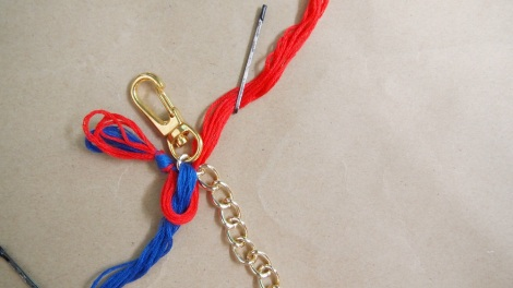 4. Place the red threads over the blue threads & loop through the same chain from underneath.