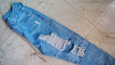 2. Fold the jeans into half and snip the other side accordingly.